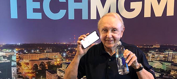 a picture of John Ed Mathison standing in front of a tech conference banner, holding a bottle of smart water and an apple iphone, in order to illustrate the tongue-in-cheek point he's making about spiritual smartness