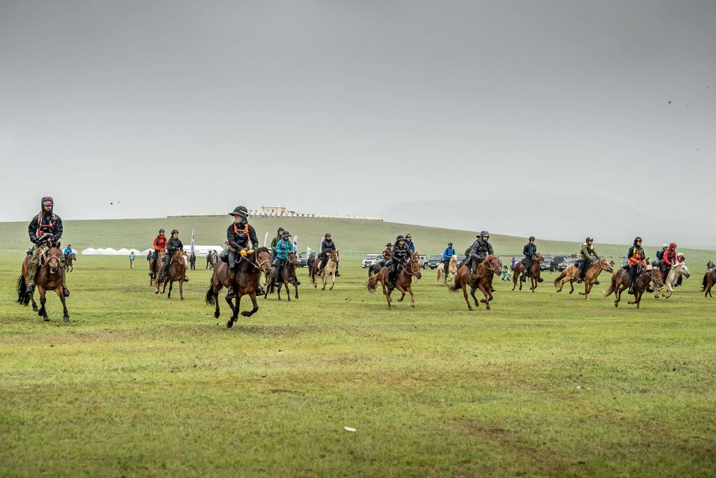 Dozens of horseback riders racing during the Mongol Derby on the Mongolian plains with a hill in the background