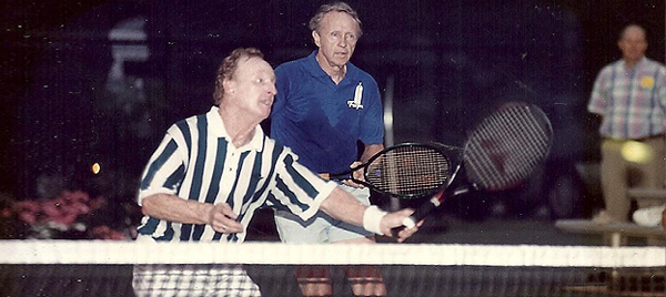 An older picture of John Ed Mathison playing doubles tennis at a charity event with his partner, two-time grand slam champion and men's tennis legend Rod Laver