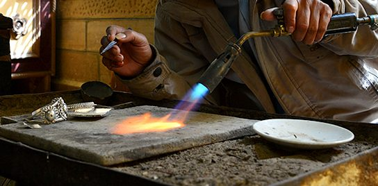 Silversmith refining silver with a blowtorch in a studio.