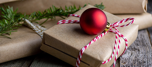 Christmas presents wrapped in brown paper with red and white string and a red ornament on top.