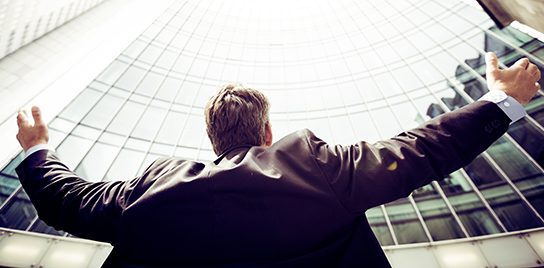 Successful man in a business suit raises his arms in front of a skyscraper.