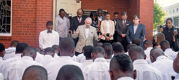 John Ed leading prayer on the steps of Valiant Cross Academy.