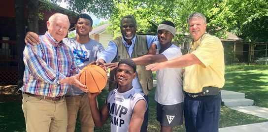 John Ed standing with a group of people of multiple races, together in harmony, holding a basketball.