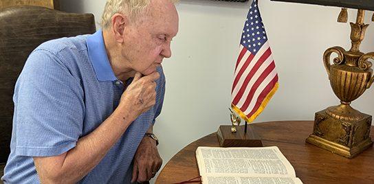 John Ed reading a Bible near an American flag.