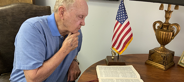 John Ed reading a Bible near an American flag.