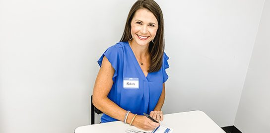 A woman with a name tag writing out name tags.