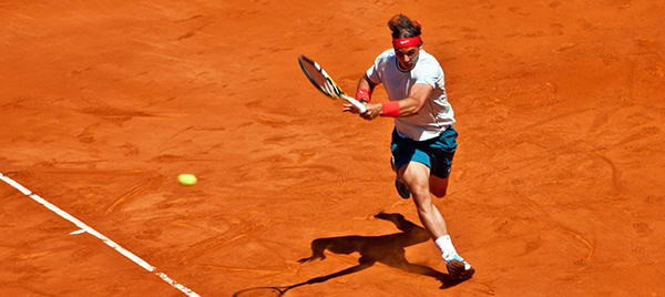 Rafael Nadal playing on a clay court.