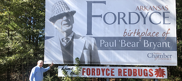 John Ed in front of the sign for Fordyce, advertising it as the birthplace of Bear Bryant.